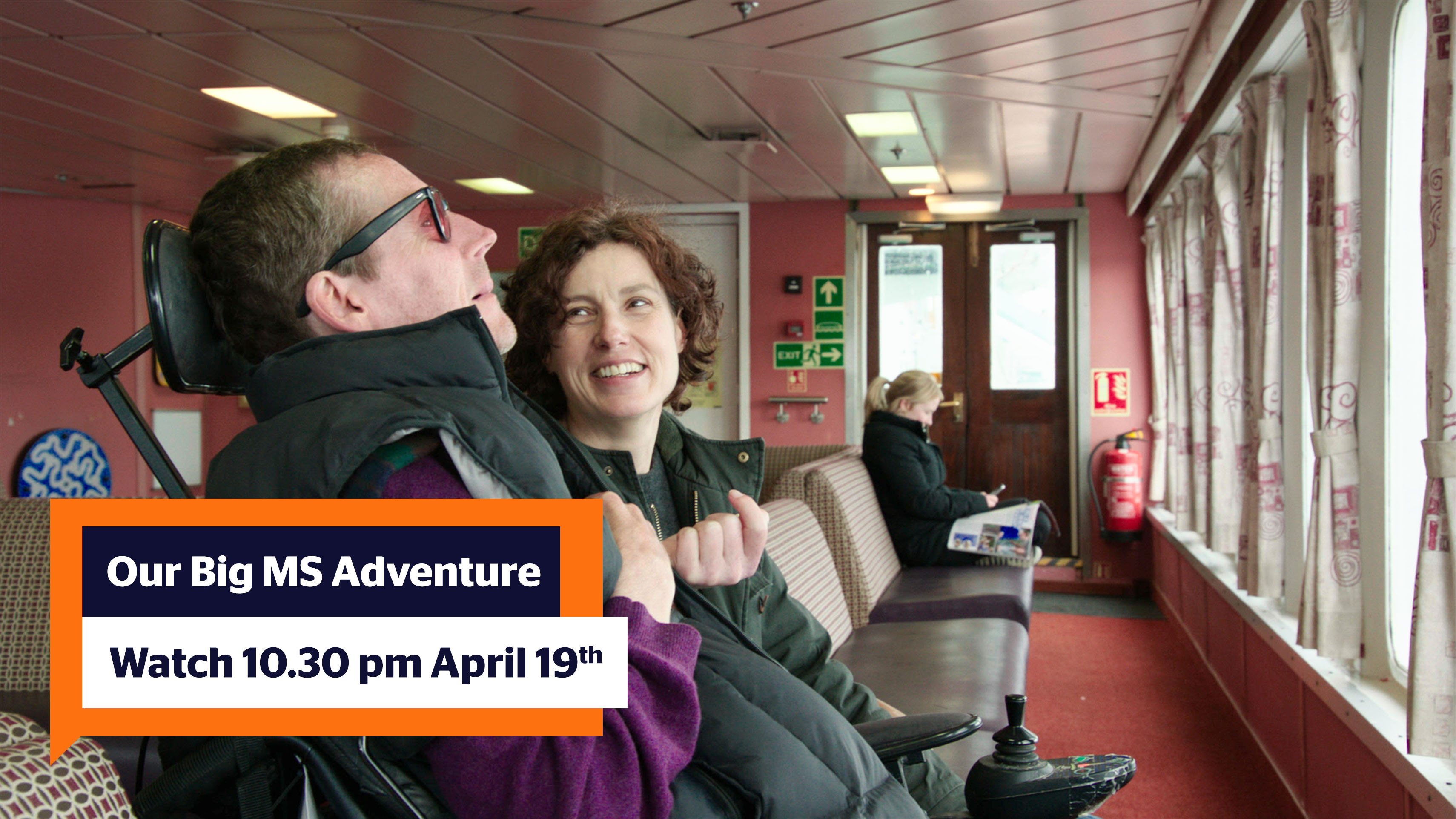 "A picture of wheelchair bound Al, who is facing to the right and Elizabeth is next to him smiling with short curly brown hair. They are in a ferry waiting lounge with salmon walls and brown sofas. There is an orange text box in the bottom left corner reading ""Our Big MS Adventure; Catch it 19th April at 10.30 pm"")"