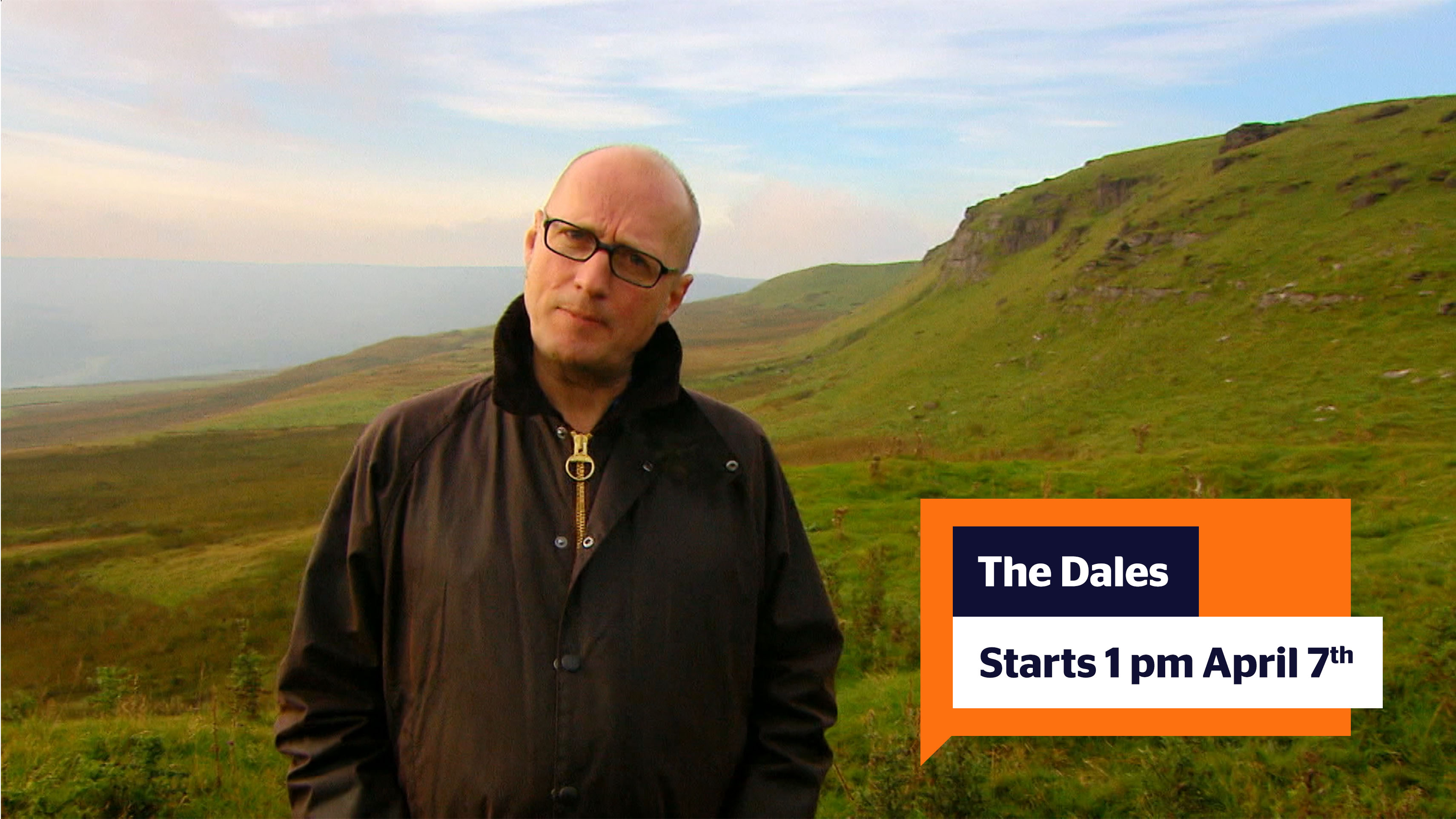 "A still from the series 'The Dales' of Adrian Edmondson (a bald man in his forties with black rectangular glasses and a black fleece coat on)facing the camera with a backdrop of the Yorkshire dales; green hills rolling for miles and a blue sky with some clouds. IN the bottom right corner is an orange speech bubble with the text ""The Dales; starts 1 pm April 7th)"