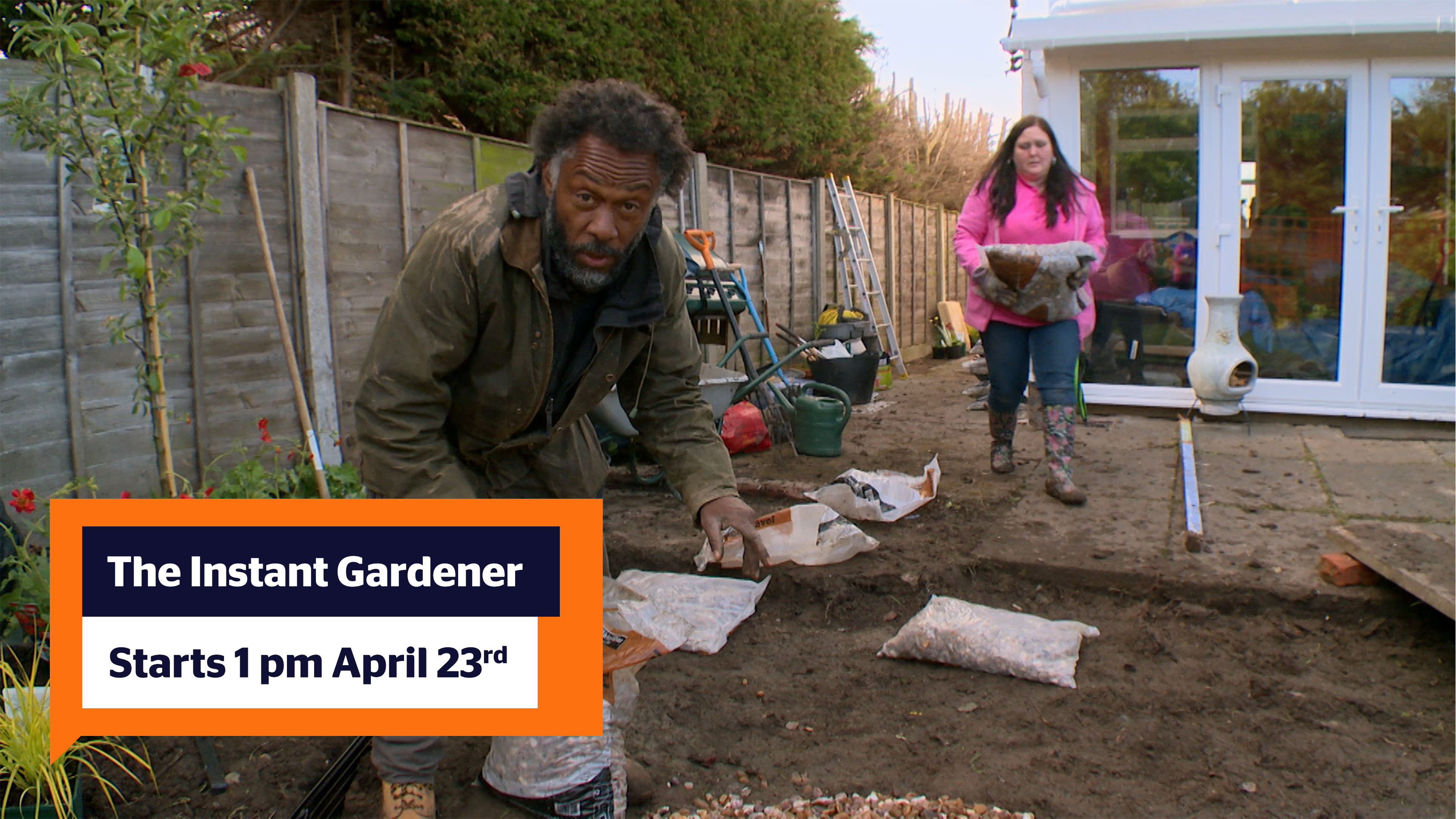 "A photo from the Instant Gardener. Danny Clarke (who is looking a the camera wearing a khaki coat and has black hair and a grey and black beard) is bent over a back of gardening supplies in a garden that is full of gardening tools and is in the middle of being renovated. On his right in the background is a lady with long black hair wearing a fuchsia coat, Demin trousers and floral wellies walking towards him holding a bag of gardening supplies. In the bottom left corner is a speech bubble reading ""The Instant Gardener: starting 23rd April at 1 pm"""